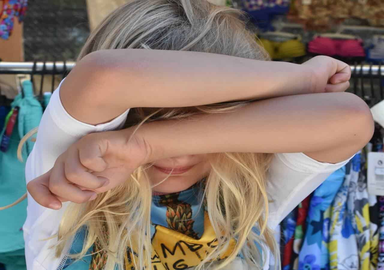 Help children with transitions. Girl hiding face - overwhelmed with transition.